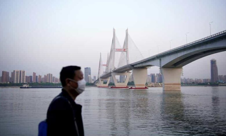 A man wearing a face mask is seen under a bridge of Yangtze river in Wuhan after the lockdown was lifted, on April 15.