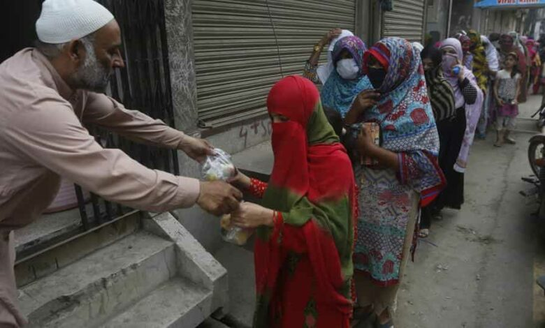 A man gives food to women for the Muslim fasting month of Ramzan, during a government-imposed Covid-19 lockdown in Lahore, Pakistan, on Wednesday.