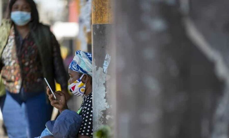 A woman wearing face masks to protect against coronavirus, holds her child whilst using a mobile phone on the sidewalk in downtown Johannesburg, South Africa, Monday, May 11, 2020.