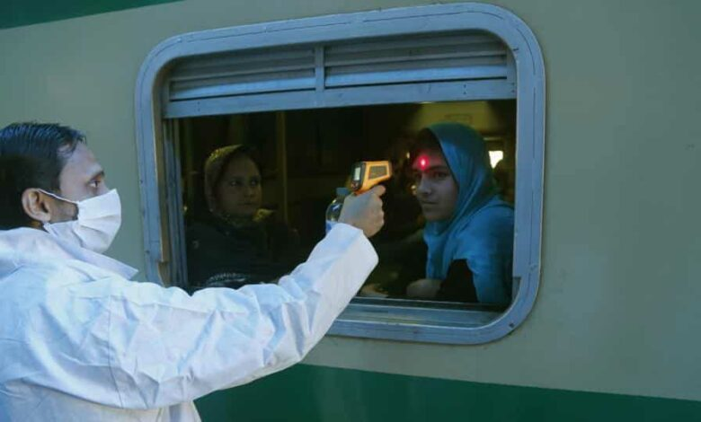 A Pakistani volunteer checks the body temperature of a passenger to help detect coronavirus, at a railway station in Lahore, Pakistan, Wednesday, March 18, 2020.