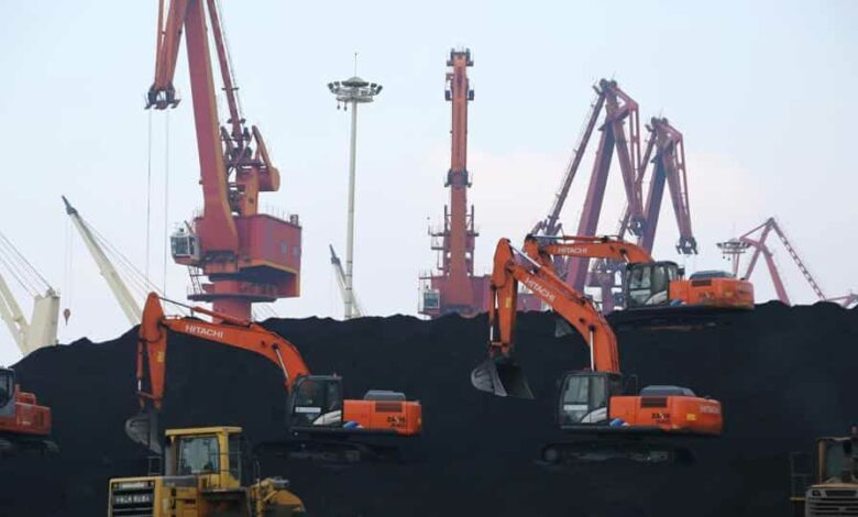 Workers operate loaders unloading imported coal at a port in Lianyungang, Jiangsu province, China.