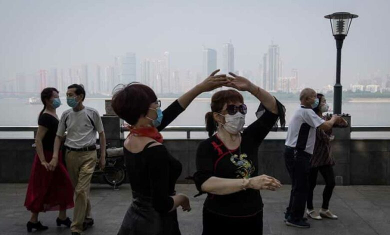 This photo taken on May 1, 2020 shows people wearing face masks as a precaution against the Covid-19 coronavirus as they dance under Wuhan Bridge in Wuhan, in China