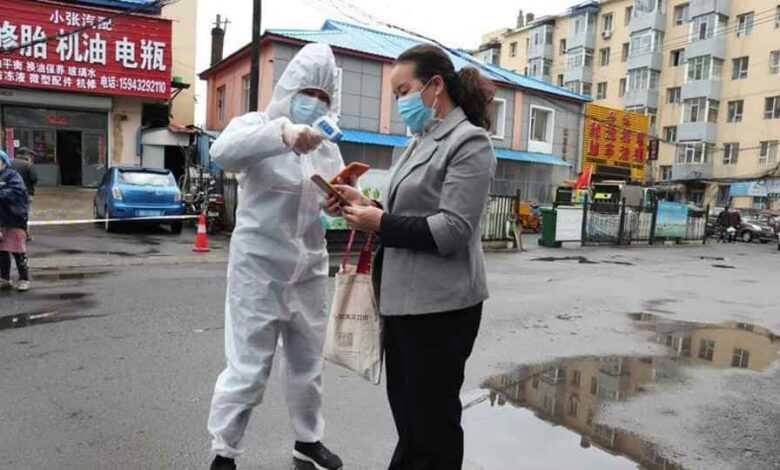 A worker in protective suit takes body temperature measurement of a woman following the coronavirus disease outbreak in Jilin, Jilin province, China.