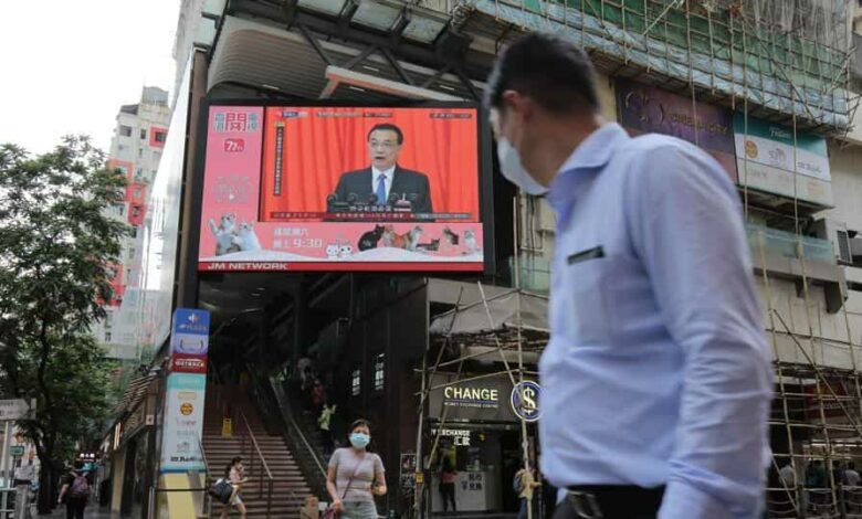Pedestrians wearing protective masks walk past a screen playing a news report on Chinese Premier Li Keqiang speaking at the National People