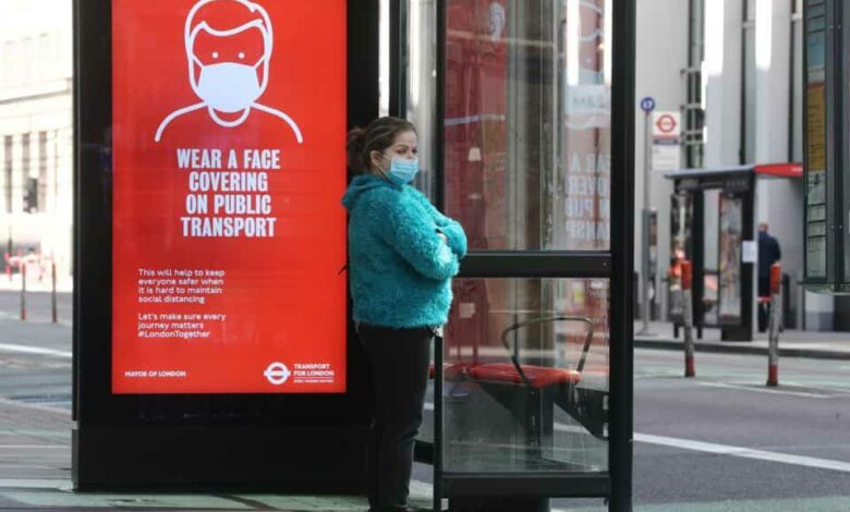 A woman wearing a face mask waits at a bus stop in London, following the outbreak of the coronavirus disease (COVID-19), London, Britain, May 18, 2020.