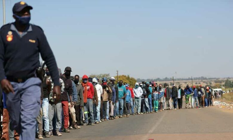 A police officer walks past people waiting in queues for food aid for the second time in two weeks, after South African President Cyril Ramaphosa said he aims to further ease restrictions imposed to curb the coronavirus disease (COVID-19) outbreak, in Sunderland Ridge, South Africa, May 14, 2020.