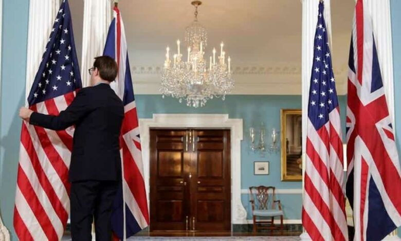 A State Department employee adjusts flags before a cancelled bi-lateral photo between US Secretary of State Rex Tillerson and British Foreign Minister Boris Johnson at the State Department in Washington, US March 22, 2017.