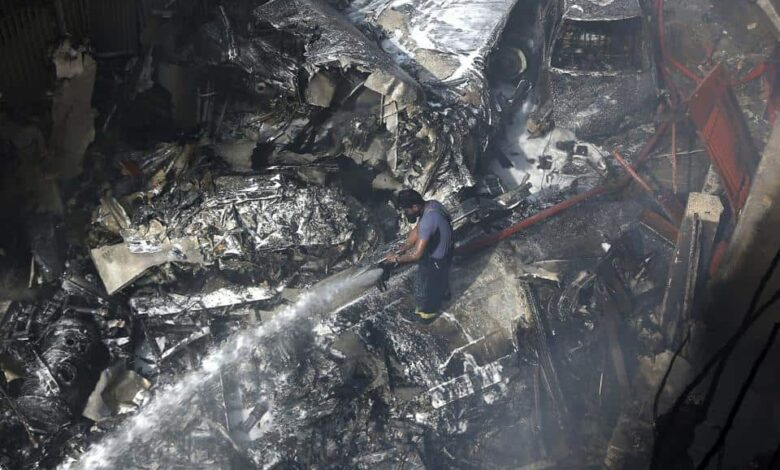 A firefighter tries to put out fire caused by plane crash in Karachi, Pakistan, Friday, May 22, 2020.