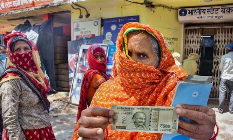 An elderly woman shows a Rs 500 after withdrawing from her Jan Dhan account, Mathura, May 4, 2020