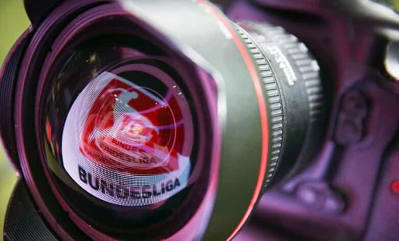 A LED board showing the Bundesliga logo is reflected in a lens prior to the Bundesliga match.