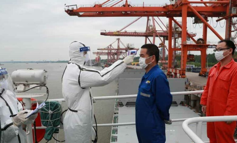 A staff member in protective suit takes body temperature measurement of a crew worker of a cargo ship bound for Japan following the coronavirus disease (Covid-19) outbreak, at a container terminal at a port in Wuhan, Hubei province, China.
