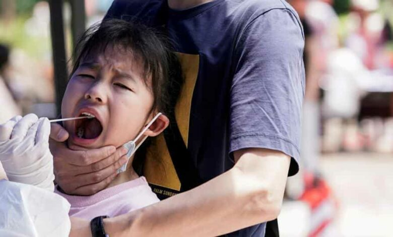A child reacts while undergoing nucleic acid testing in Wuhan, the Chinese city hit hardest by the coronavirus disease (COVID-19) outbreak, Hubei province, China May 16, 2020.