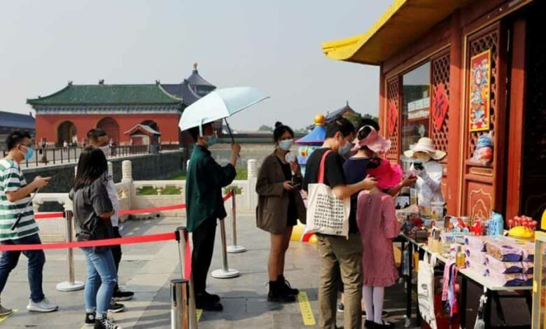 Visitors wearing face masks practise social distancing as they line up outside a souvenir shop at the Temple of Heaven, or Tiantan Park, on the first day of the five-day Labour Day holiday following the coronavirus disease (COVID-19) outbreak, in Beijing.