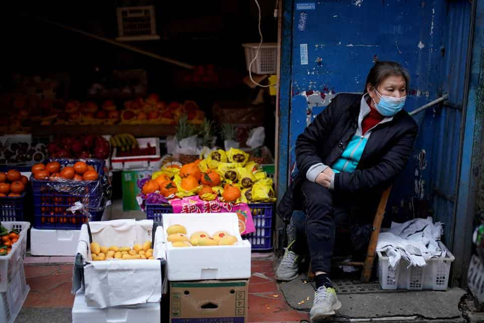 FILE PHOTO: A woman wearing a face mask sits next to a fruit stall at a residential area after the lockdown was lifted in Wuhan, capital of Hubei province and China