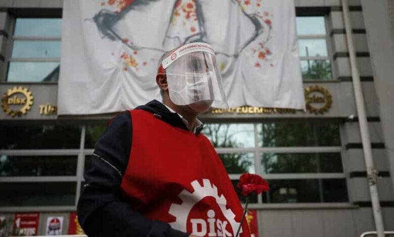 A demonstrator from the Confederation of Progressive Trade Unions of Turkey, or DISK, wearing a face mask and shield for protection against coronavirus, gather during May Day protests in Istanbul.