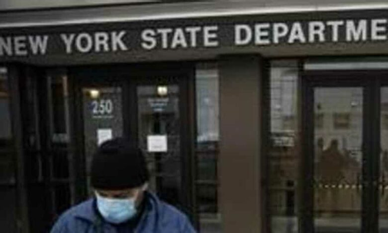 Visitors to the Department of Labor are turned away at the door by personnel due to closures over coronavirus concerns, Wednesday, March 18, 2020, in New York. Applications for jobless benefits are surging in some states as coronavirus concerns shake the U.S. economy.