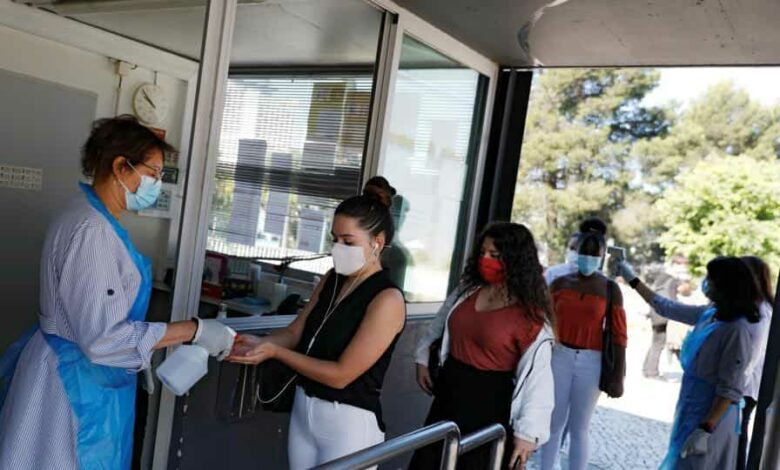 A student wearing a protective face mask uses hand sanitizer upon arrival at D. Pedro V High School, as grade 11 and 12 high school students return to schools under strict restrictions, during the coronavirus disease  outbreak, in Lisbon, Portugal.