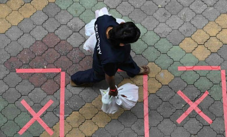 A security guard carrying bags of takeaway food walks past safe distance markers, as a protective measure against the spread of the Covid-19 novel coronavirus, in Singapore on May 2, 2020.