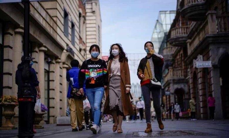 People wearing face masks are seen at a main shopping area in China's Wuhan after lifting of lockdown on April 14.
