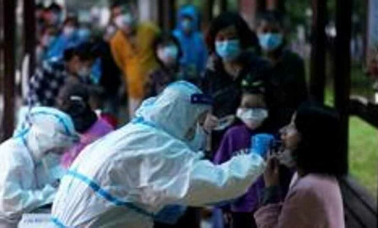 A medical worker in a protective suit conducts a nucleic acid testing for a resident as people wearing face masks queue behind for testings, at a residential compound in Wuhan, the Chinese city hit hardest by the coronavirus disease (COVID-19) outbreak, Hubei province, China
