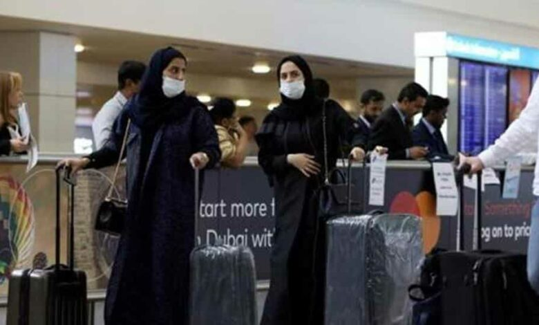 Travellers wear masks as they arrive at Dubai International Airport, after the UAE