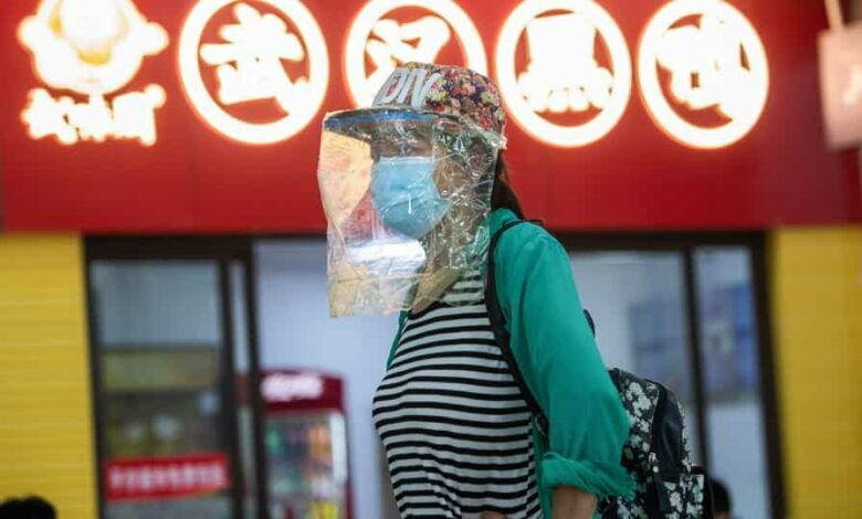 A passenger wearing a face shield is seen at a long-distance bus station in Wuhan in China