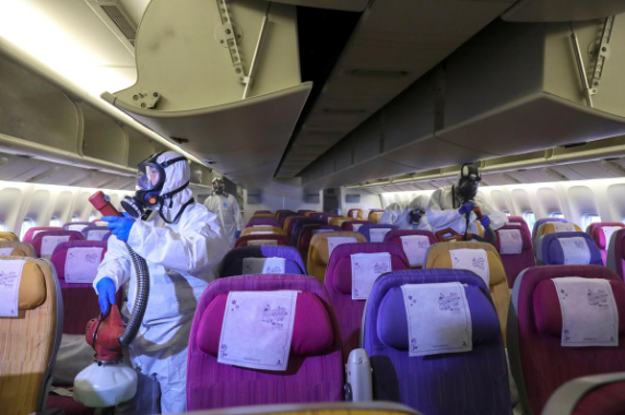 Members of the Thai Airways crew disinfect the cabin of an aircraft of the national carrier during a procedure to prevent the spread of the coronavirus at Bangkok