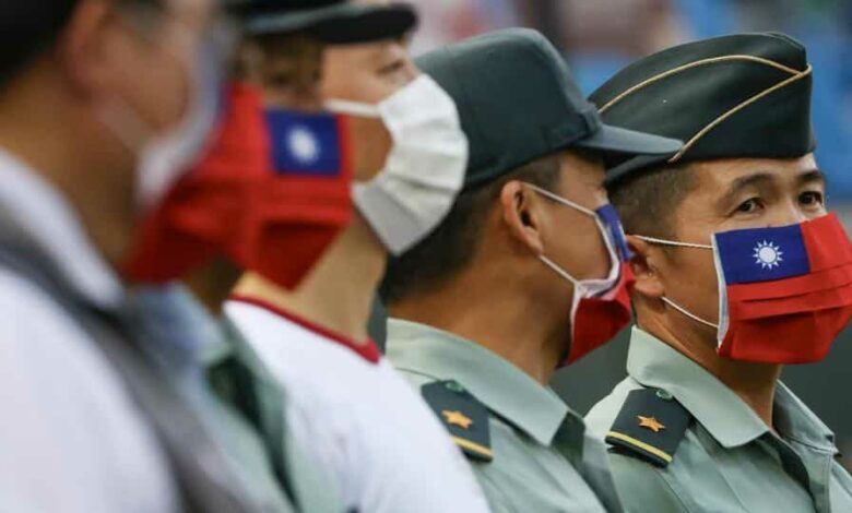 Army representative are seen at the opening of a baseball game with face masks decorated as a Taiwan flag to protect themselves from the coronavirus disease (Covid-19).