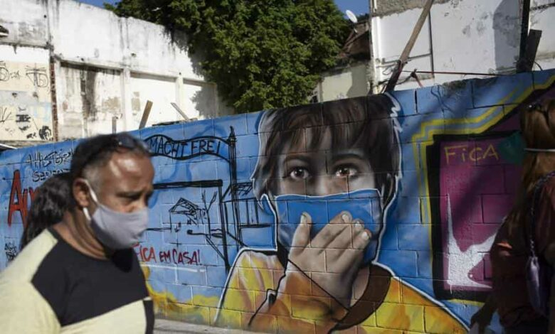 A man walks past a mural referencing the COVID-19 pandemic, painted in honor of health workers in Rio de Janeiro, Brazil, Thursday, May 21, 2020.
